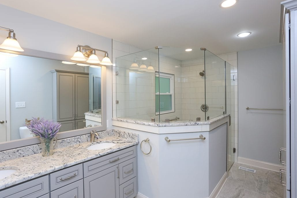large bathroom with walk in shower and granite sink