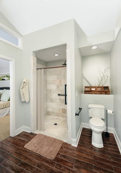 Small bathroom with walk in shower and wood-like tile on the floor.