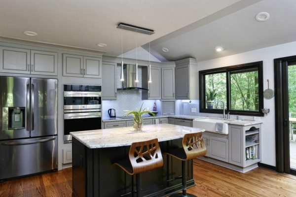 Open concept kitchen with large island and white granite countertops.